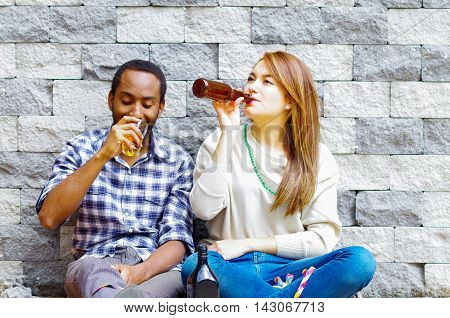 Interracial couple wearing casual clothes sitting towards grey brick wall enjoying some drinks and each others company.