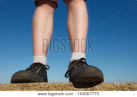 Male feet wearing black sneakers outdoor wide angle view