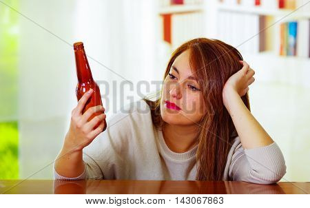Woman wearing white sweater sitting by bar counter lying over desk staring at beer bottle, drunk depressed facial expression, alcoholic concept.