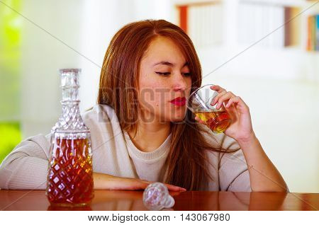 Woman wearing white sweater sitting by bar counter lying over desk next to glass and bottle, drunk depressed facial expression, alcoholic concept.