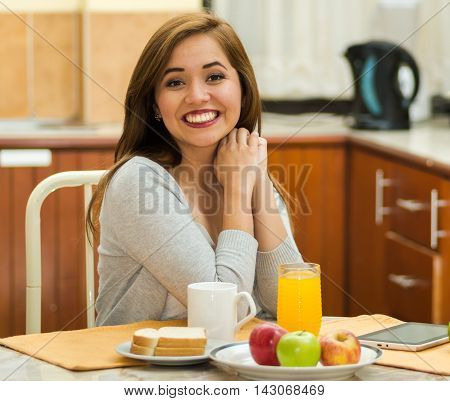 Young pretty brunette sitting by breakfast table smiling to camera, fruits, juice and coffee placed in front, hostel environment.