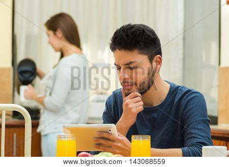 Young handsome man seated by breakfast table looking at tablet screen, girl standing behind pouring hot water, fruits, juice placed in front, hostel environment.