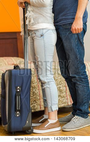 Closeup legs of couple wearing jeans, standing next to bed, blue suitcase on floor, hostel concept.