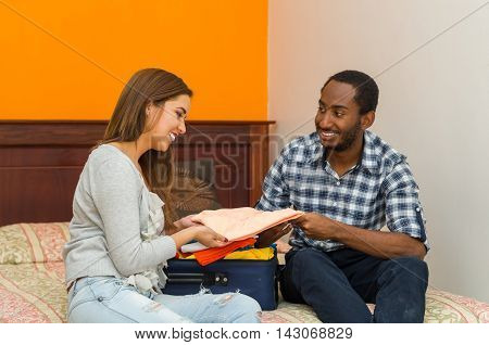 Charming young couple sitting on bed interacting happily while packing suitcase with clothes, hostel guest concept.