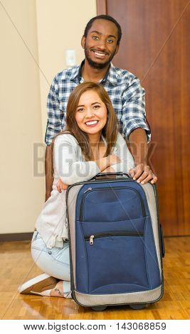 Charming young couple wearing casual clothes sitting down posing for camera smiling, blue suitcase standing on floor, hostel guest concept.