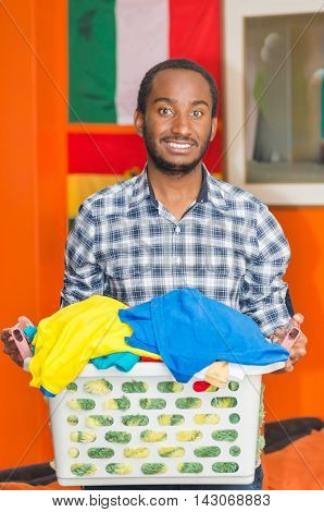 Young handsome man wearing casual clothes holding laundry basket and smiling to camera, orange wall with flags in background, hostel guest concept.