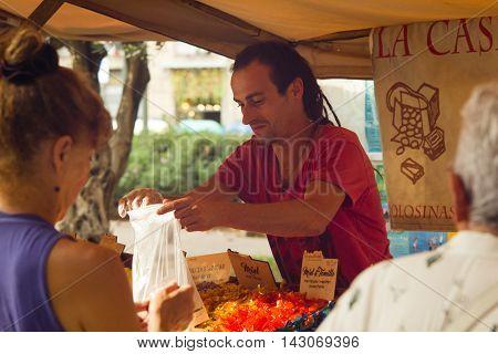 Barcelona Spain 16 august 2016: Street stall seller passes purchase to the customer