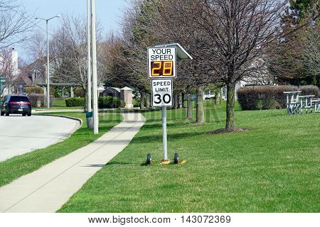 A radar speed sign indicates that a vehicle is approaching at 28 miles per hour.