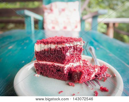 Cutting red velvet cake on green table with blurred chair in the morning at coffee shop surrounded by nature in Chiangmai Thailand (Horizontal)
