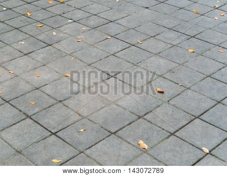 Square pattern of dirty cement floor with dried leaves Close-far perspective view