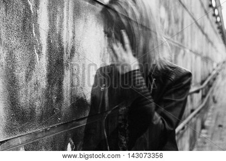 Young woman suffering from a severe disorientation confusion or sadness outdoors in front of a wall. Converted to black and white grain added blurry slightly out of focus.
