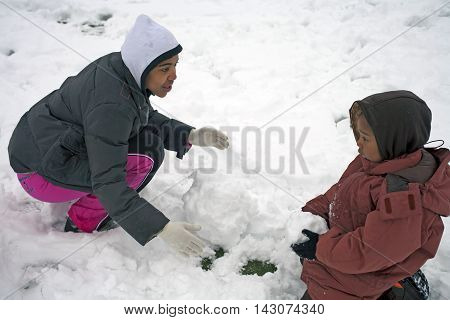 BRONX NEW YORK - FEBRUARY 22: Mother with child play with snow in park after snow storm. Taken February 22 2009 in New York.