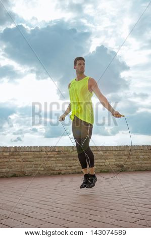 Young man jumping rope sky sunny day lens flare