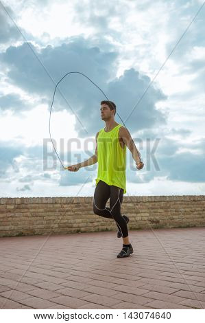 Young man jumping rope sky sunny day
