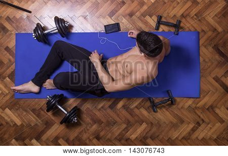 Young Man Relaxing Smartphone Elevated View Exercise Mat