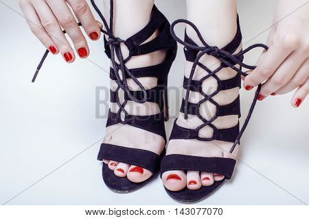 fashion concept people: woman with red nails manicure pedicure tying shoelaces on hight heel shoes isolated on white background close up