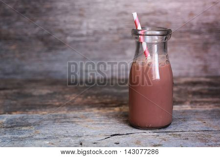 Bottle of chocolate milk with red striped straw on wooden background