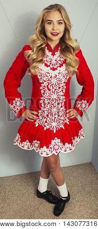 Beautiful blond girl doing Irish dance in red and white costume