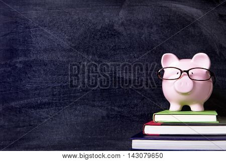 Piggybank with glasses and blackboard background copy space