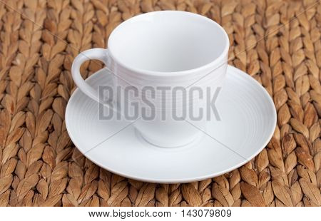 white ceramic earthenware cup white saucer straw wicker stand