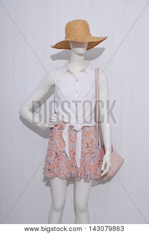female dress with hat ,bag on dummy-wooden background