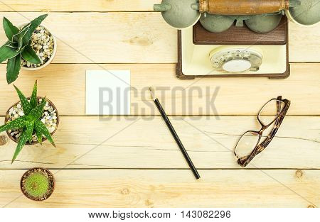 Topview of wooden table with office tools and plant. Mock up