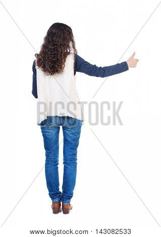 Back view of  woman thumbs up. Rear view people collection. backside view of person. Isolated over white background. Long-haired girl with curly hair shows thumb up at arm's length.
