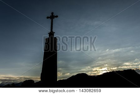 Cross in front of sunset and cloudy sky