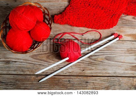 Natural woolen yarn and knitting on vintage wooden background