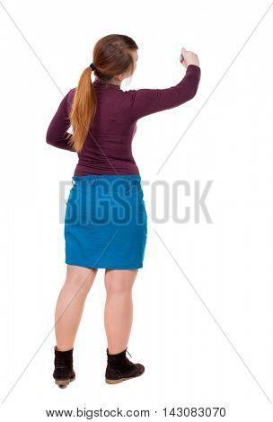 back view of writing beautiful woman. Young girl in dress. Rear view people collection.  backside view of person. Isolated over white background. Girl with red hair tied in a pigtail draws felt-tip