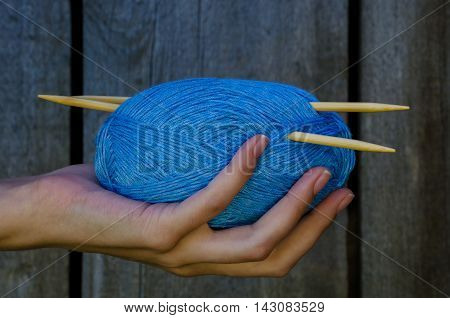 Female Hand Holding A Cotton Yarn Ball With Knitting Needles