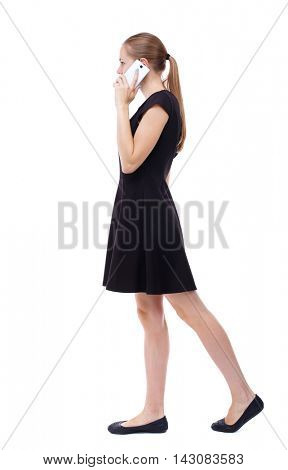side view of a woman walking with a mobile phone. back view of girl in motion.  backside view of person.  Rear view people collection. Isolated over white background. Blonde in a short black dress is