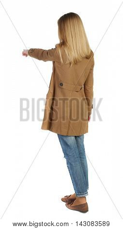Back view of  pointing young women in parka. Young girl gesture. Rear view people collection.  backside view of person.  Isolated over white background. The blonde in a brown cloak, points a finger
