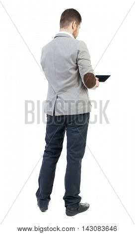 back view of business man uses mobile phone.    rear view people collection. Isolated over white background. backside view of person. The bearded man in a gray jacket, working on the tablet.