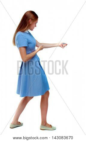 back view of standing girl pulling a rope from the top or cling to something. girl  watching. Rear view people collection.  backside view of person.  Isolated over white background. Skinny girl in a