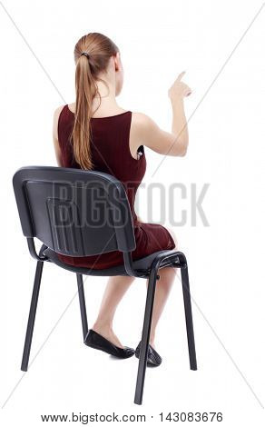 back view of young beautiful  woman sitting on chair and pointing.  girl  watching. Rear view people collection. A girl in a burgundy dress sitting on a chair selects an answer.
