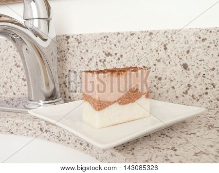 Pink and white natural handmade soap bar on a white ceramic soap dish set on a granite bathroom counter top by a faucet