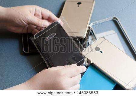 Plastic mobile phone cases on gray background. Choosing new cover for smartphone. Cheap bad-quality accessories variety