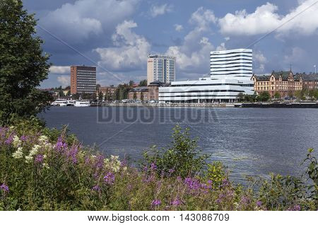 UMEA, SWEDEN ON JULY 14. View of the waterfront to the town on July 14, 2016 in Umea, Sweden. River, hotels and boardwalk. Showers in the background. Editorial use.