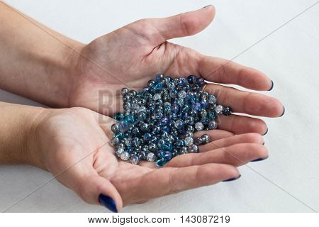 Blue glass beads on woman hands on white background