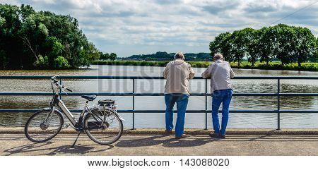 Two elderly men leaning over a bridge railing and looking musing over the water. Next to them an e-bike is parked.