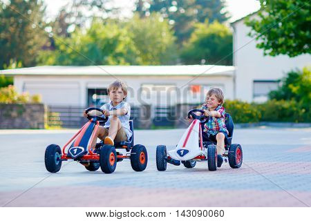 Two active little kid boys driving pedal race cars in summer outdoors. Children, best friends racing with fast speed and having fun. Twins making competition