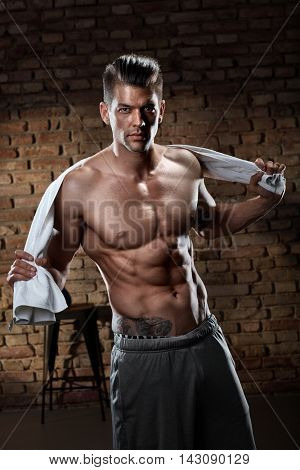 Portrait of muscular handsome shirtless man after workout, looking at camera.