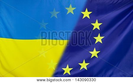 Ukraine and European Union relations concept with diagonally merged real fabric flags