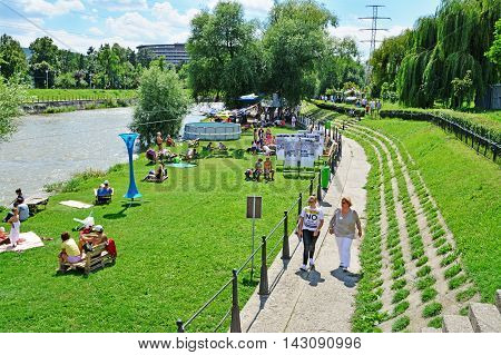 CLUJ-NAPOCA ROMANIA - AUGUST 14 2016: Unidentified people with their families take a sunbath and socialize on the river banks in summer.