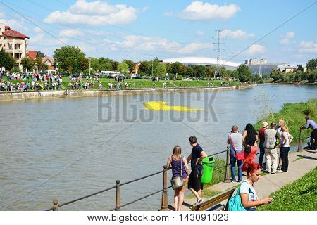CLUJ-NAPOCA ROMANIA - AUGUST 14 2016: Rubber duck race down the river for charity purposes. People following the floating rubber ducks.