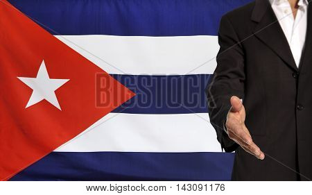 Businessman with an open hand waiting for a handshake concept for business with the Cuba flag in the background