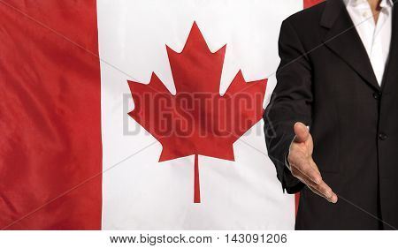 Businessman with an open hand waiting for a handshake concept for business with the Canada flag in the background