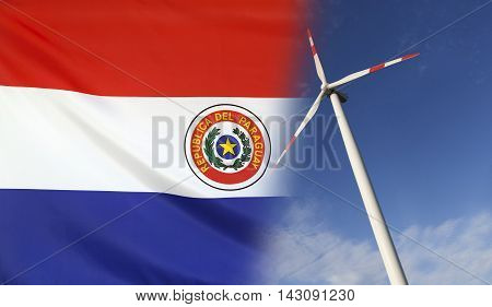 Concept clean energy with flag of Paraguay merged with wind turbine in a blue sunny sky