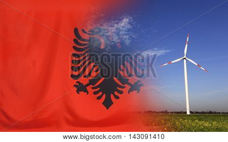 Concept clean energy with flag of Albania merged with wind turbine in a blue sunny sky and green grass with flowers